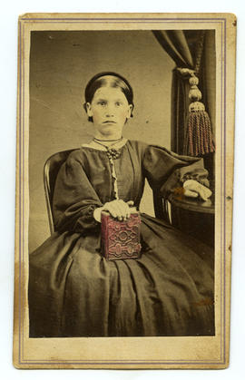 Portrait of girl (S. Francis?) holding carte de visite album