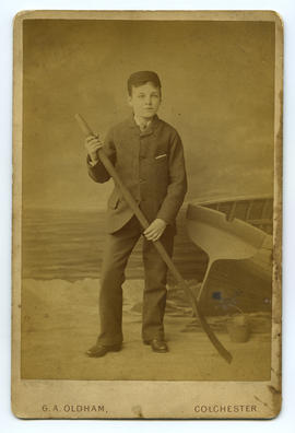 Portrait of boy holding paddle, beach setting