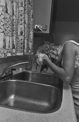 Woman washing her hair in sink and shower